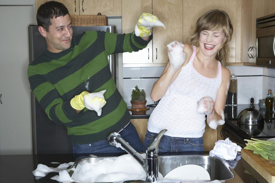 Couple washing dishes in kitchen, laughing, playing with soap suds