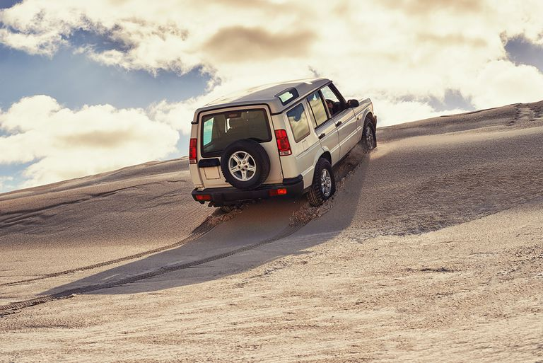 Shot of a heavy duty 4x4 driving along some sand dunes.