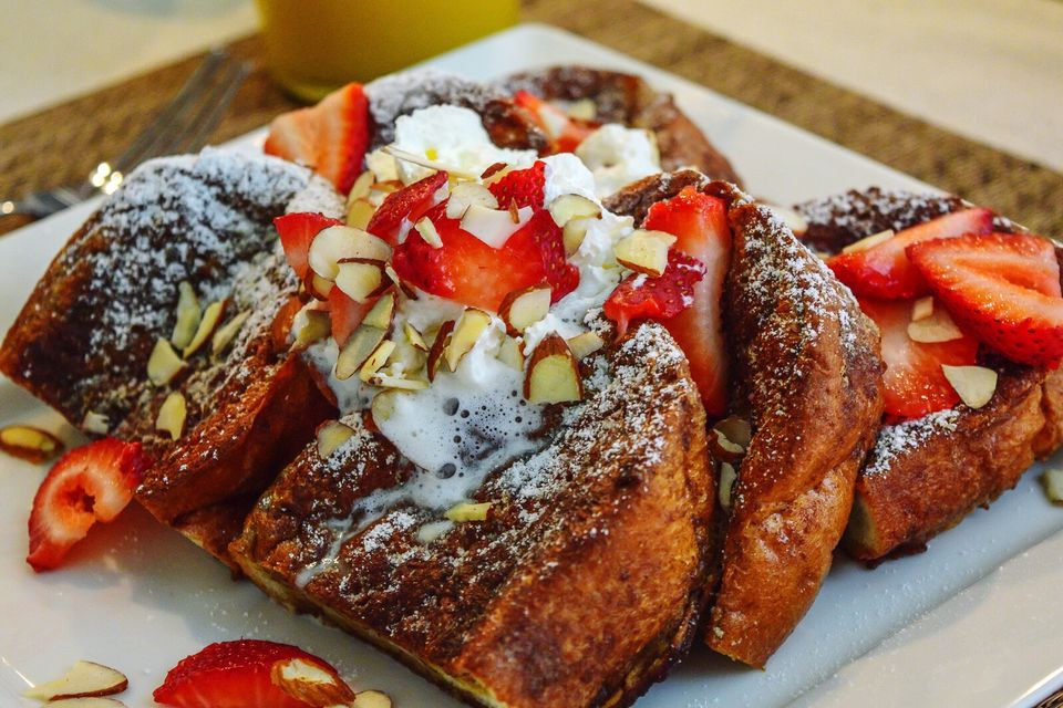 French Toast Topped With Fresh Strawberries, Sliced Almonds And Whipped Cream