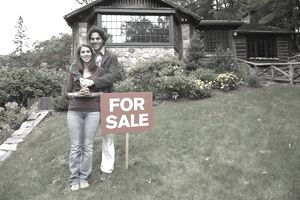 couple standing in front of home next to for sale sign