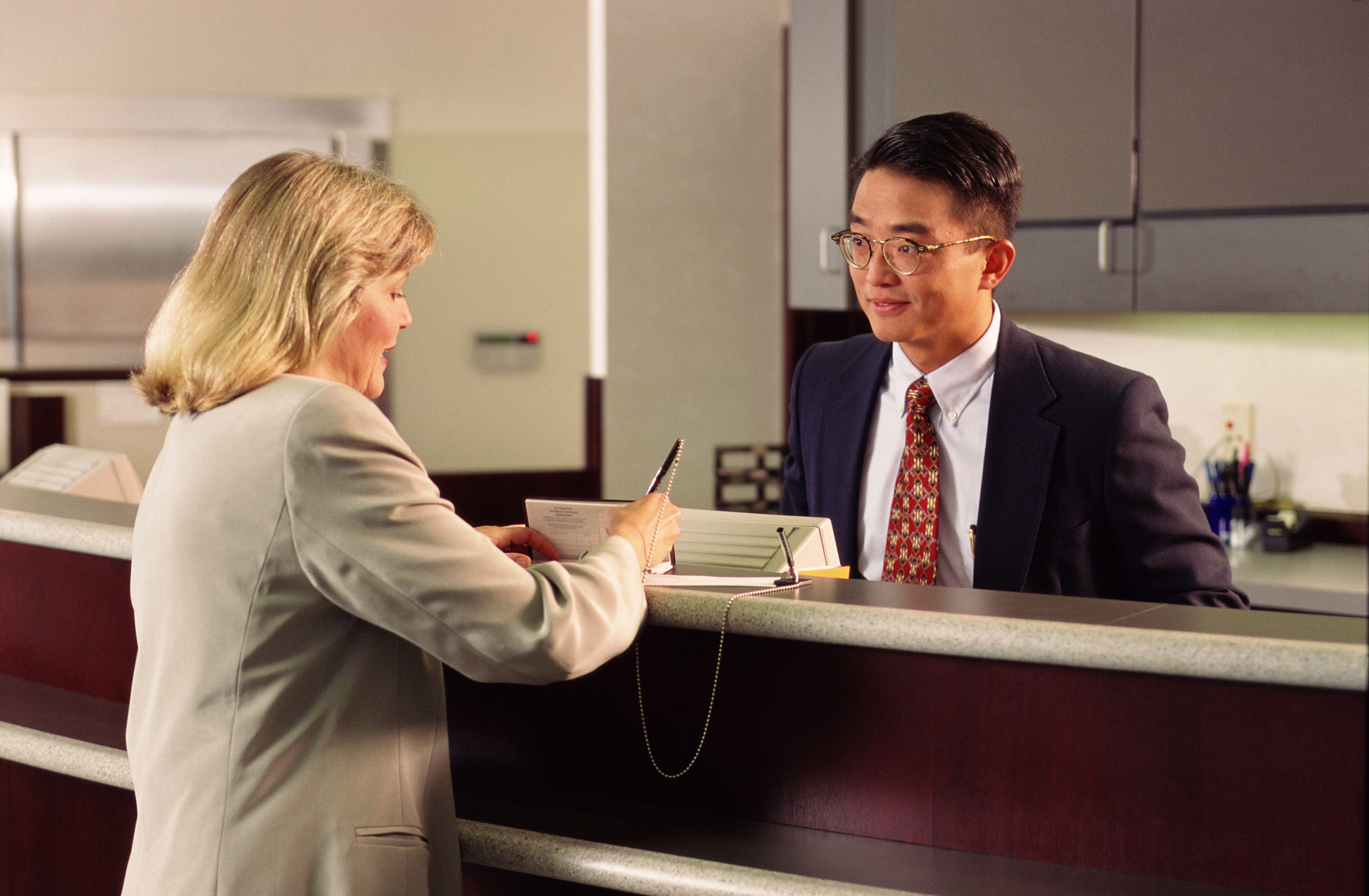 Bank Teller Job Description, Salary, and Skills