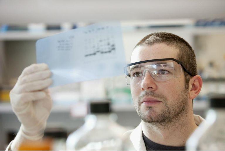 Lab technician looking at DNA sequencing gel