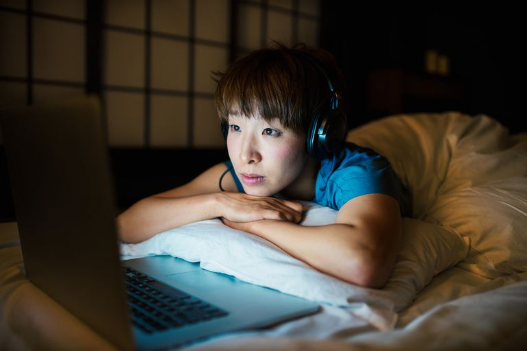woman in bed looking at laptop