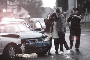 Young people and police officer at scene of car crash