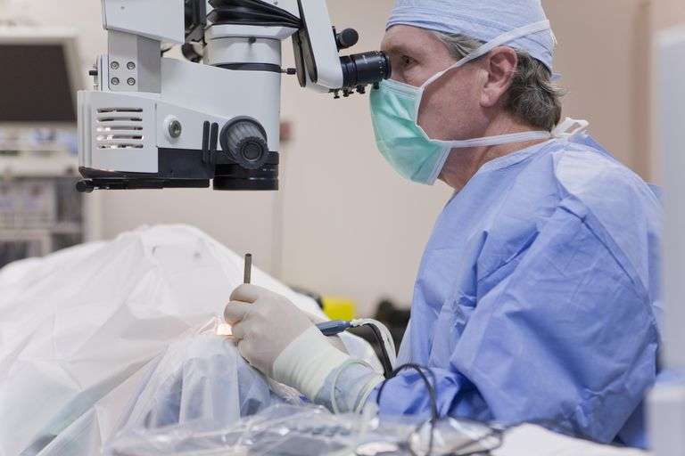 Doctor looking in microscope using a cracker instrument and phaco hand piece during cataract surgery