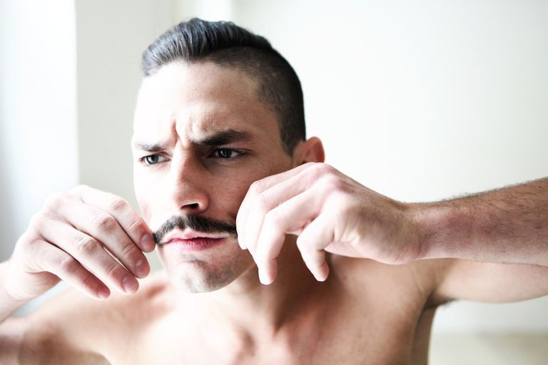 young man checking hair style and mustache