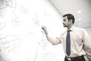 Young businessman writing on whiteboard