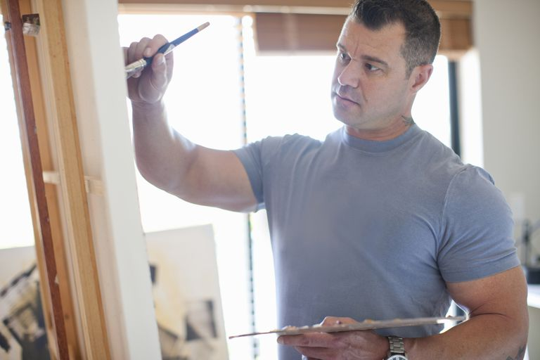 Male artist working on painting on easel