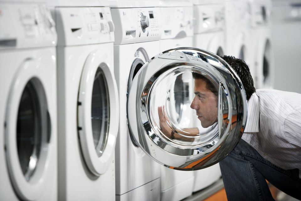 man inspecting washing machine at the store