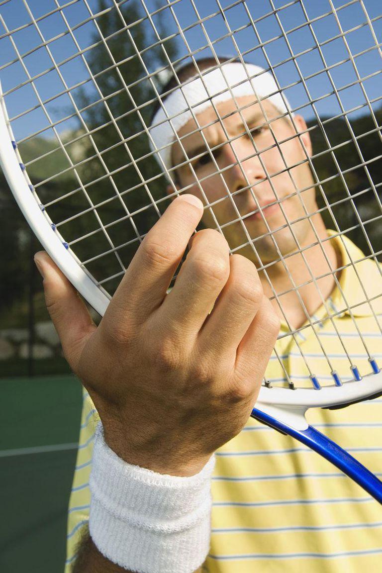 Man adjusting strings on tennis racket