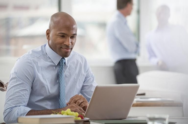 A businessman in a shirt and tie sitting at a desk, using a laptop computer