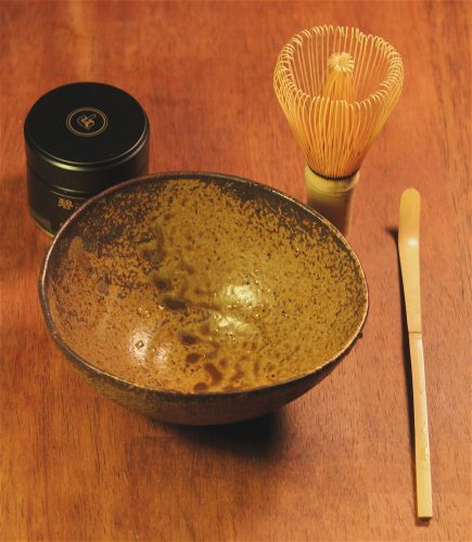 Matcha powder in a tin, a matcha whisk, a matcha scoop and a matcha bowl