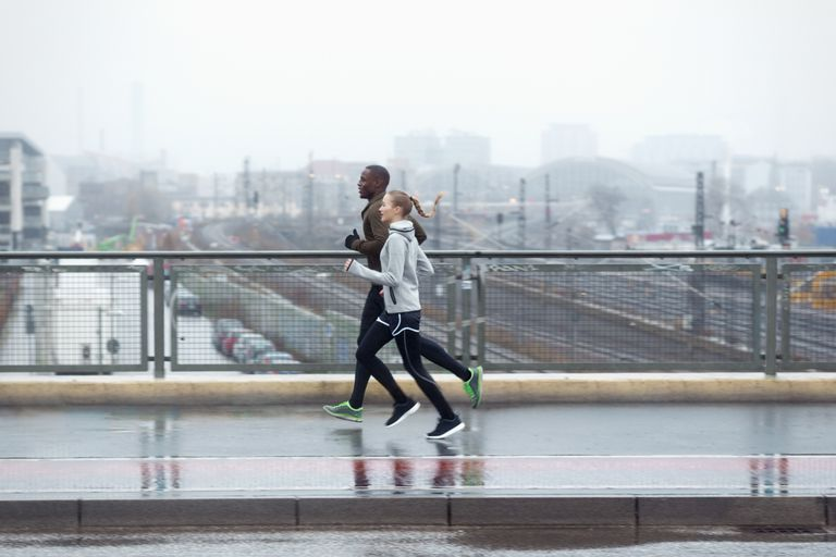 Two friends jogging across urban street bridge