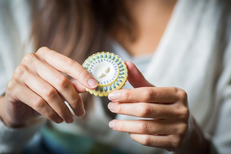 Woman with hormone replacement pill pack