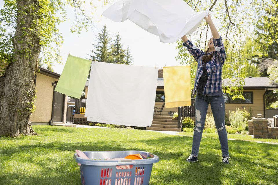 Woman folding sheets fresh from clothesline in backyard