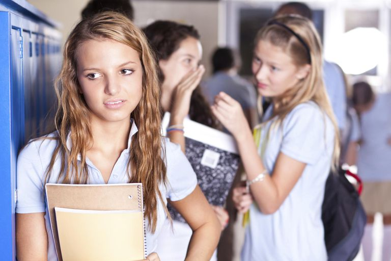 Teenage girls gossiping about another teenager
