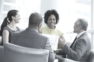 The compensation manager discusses salary ranges with other managers.