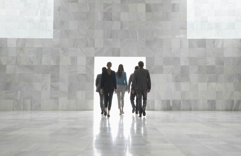 Business people walking toward doorway in modern lobby