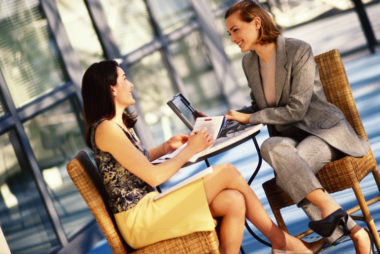 Two female executives sitting at table