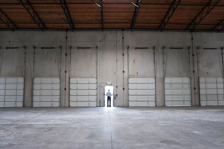 Man in doorway of shipping doc in warehouse.