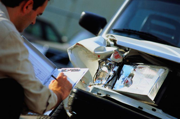 Insurance adjustor filling out form for damage report on car