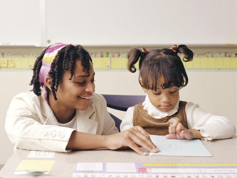 Female teacher assisting girl (3-5) in classroom, smiling
