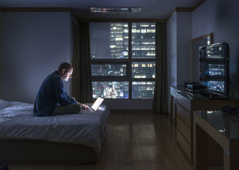 Man using laptop at night in bed