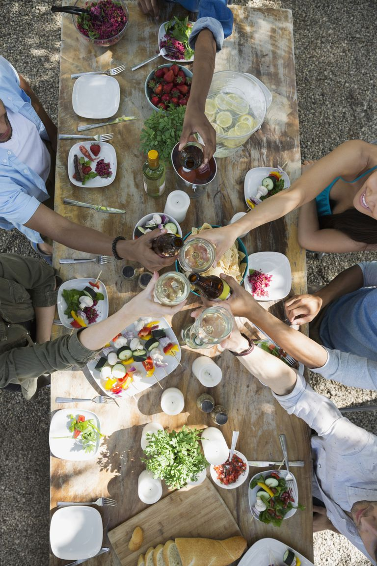 Overhead view friends toasting wine glasses patio table