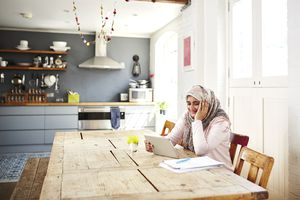 Woman working from kitchen table at home