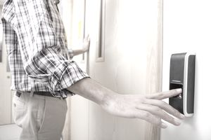 Man using finger print entry technology to open door