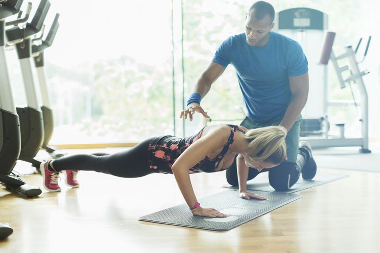 male personal trainer training woman doing plank exercise