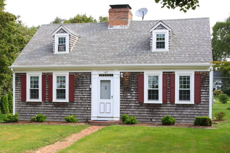 New england house with grey shingles two small dormers without shutters red shutters on