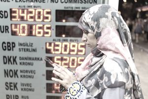 woman wearing hijab in front of currency exchange prices on an electronic board
