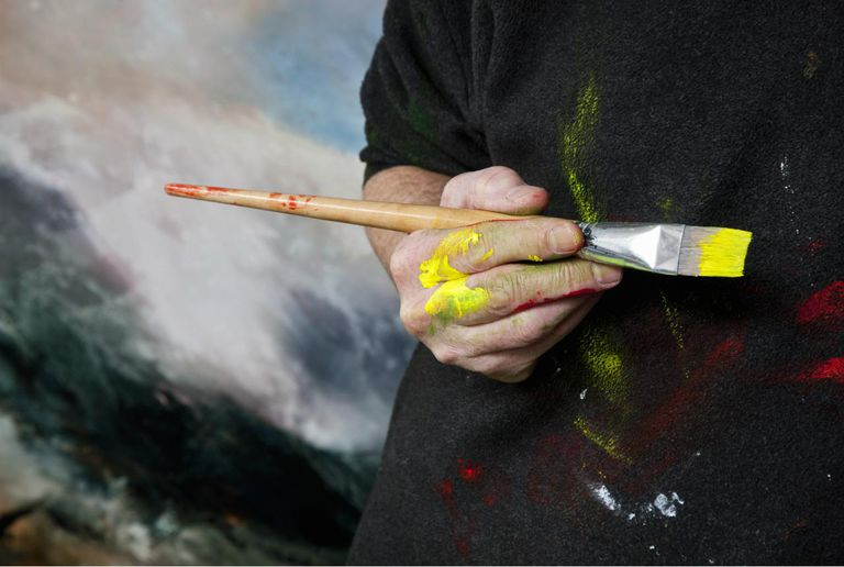 Artist in studio poised with brush in hand