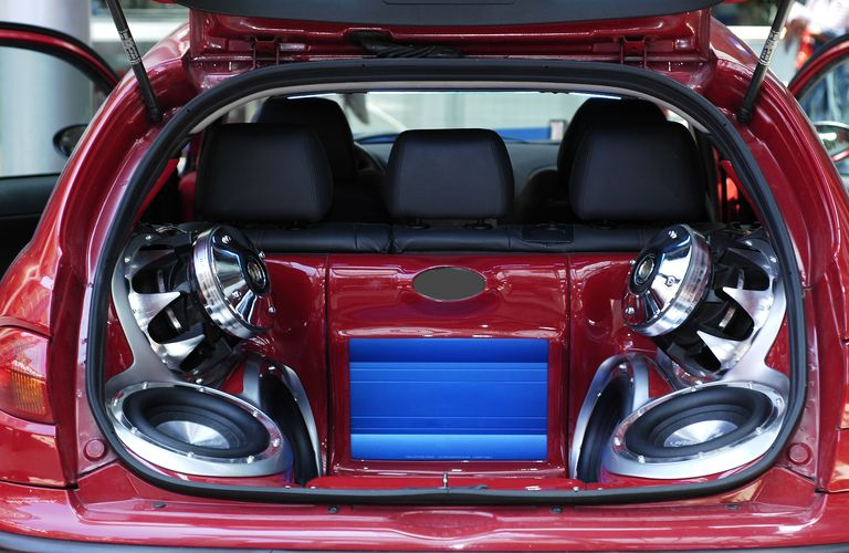 A Hi-Fi music system with speakers and subwoofers installed in the trunk of a hatchback vehicle
