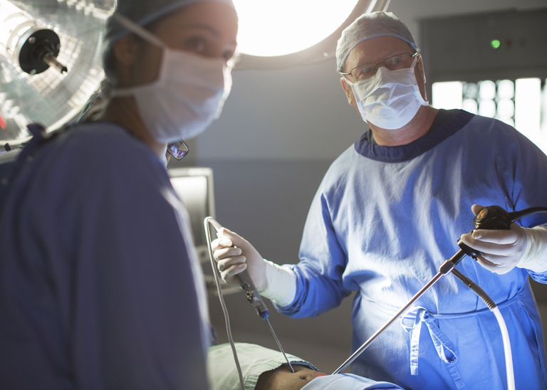 Male and female doctors performing laparoscopic surgery in operating theater