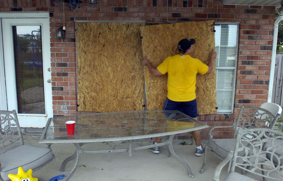 A man placing plywood over windows