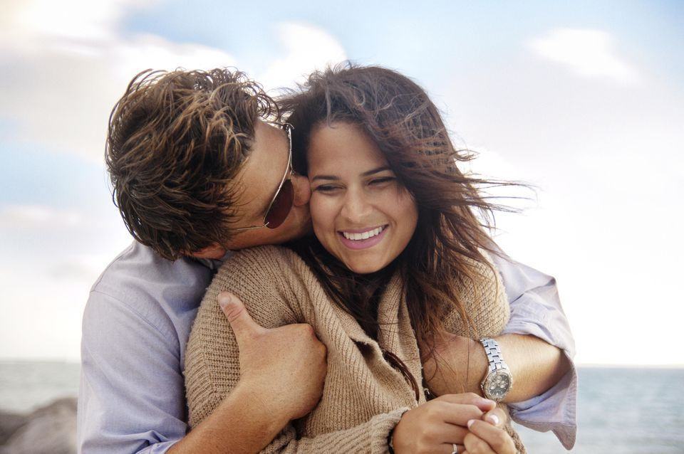 Man Kissing Girlfriend On Cheek At The Beach