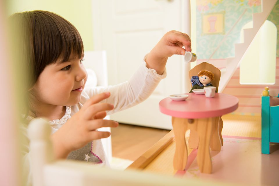 Girl playing with doll house