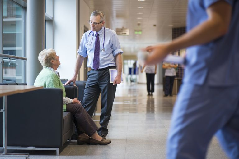 Senior woman talking to doctor in waiting room