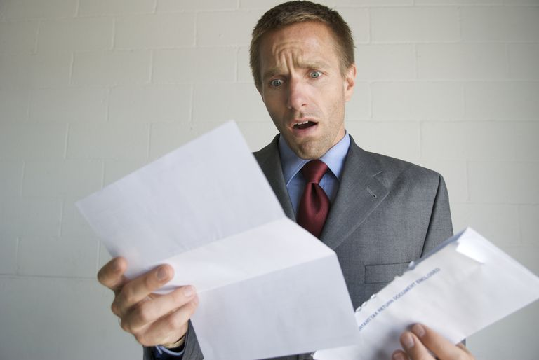 Man looking at a letter with a shocked look on his face