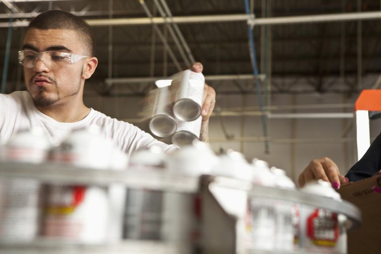 Man handles pray cans on an assembly line