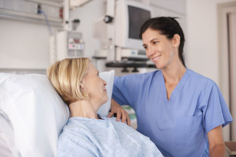 Nurse comforting patient in hospital bed
