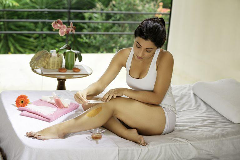 Hispanic young woman using depilation wax on her legs