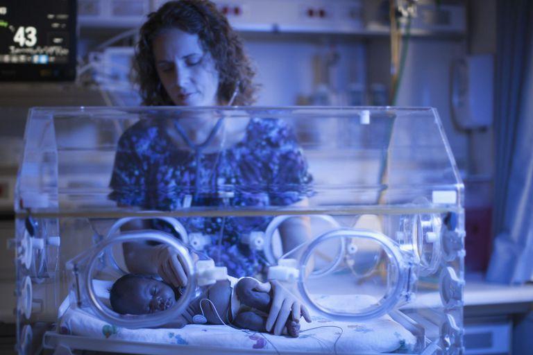Nurse tending to newborn in incubator
