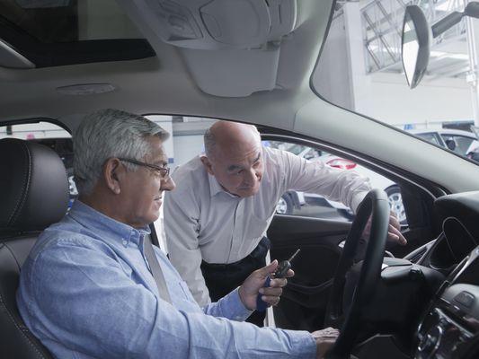 Hispanic car salesman showing customer new car