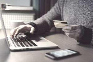 Man using debit card on computer