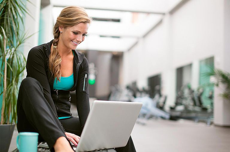 Young woman in gym corridor using laptop