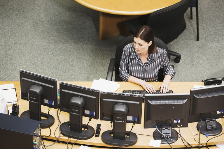Woman using computer with numerous monitors