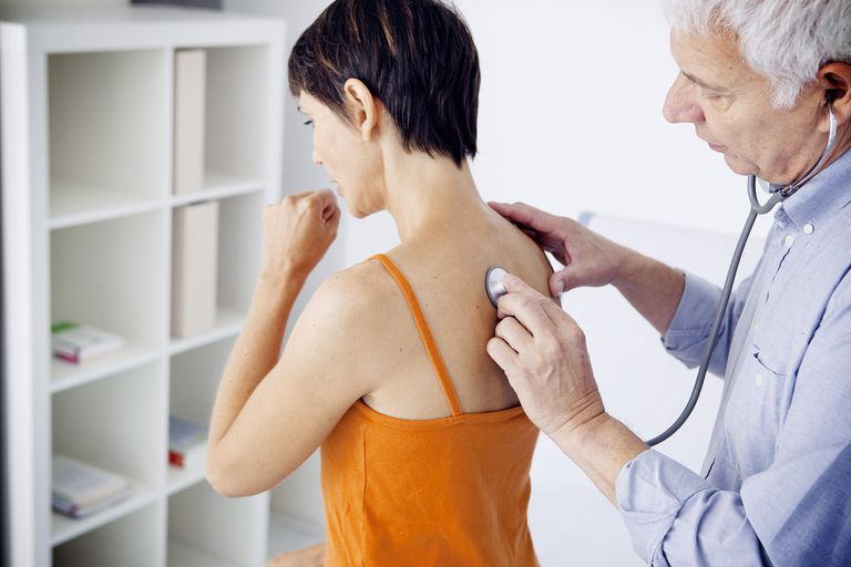 Doctor listening to woman's cough with stethoscope